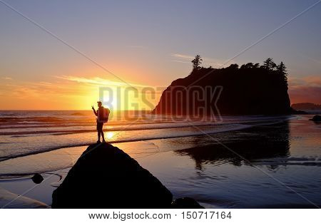Hiker Watching Sunset Over the Ocean Surf.  Ruby Beach, Olympic National Park, Washington.