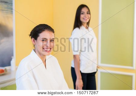 Woman beautician doctor with patient in spa wellness center. Young female professional cosmetologist made massage to beautiful brunette girl in cosmetology cabinet or beauty parlor