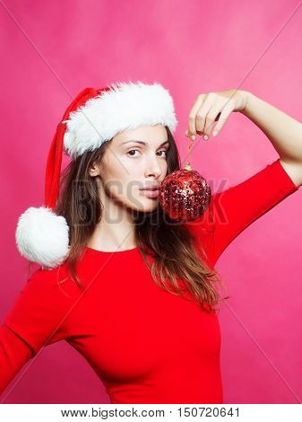 Pretty sexy brunette woman in red shirt and santas hat holding red christmas ball near mouth on red studio background