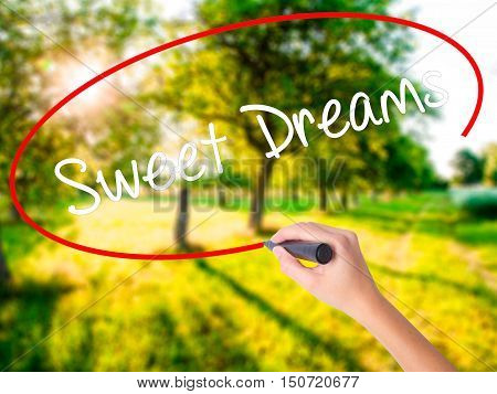Woman Hand Writing Sweet Dreams With A Marker Over Transparent Board