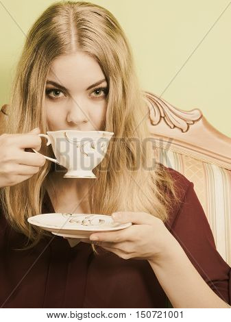 Fashionable woman drinking cup of coffee sitting on vintage sofa. Young girl with hot energizing beverage stay awake. Caffeine energy. Sepia.