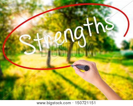 Woman Hand Writing Strengths With A Marker Over Transparent Board .