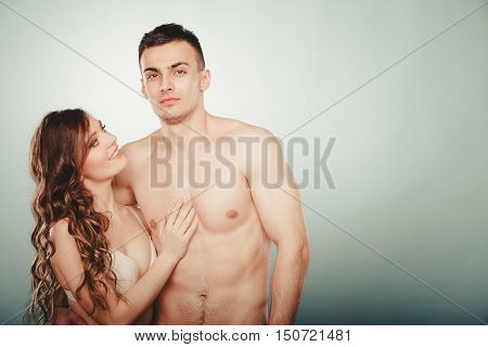 Sexy passionate young couple lovers embracing in studio. Handsome muscled half naked semi nude man and pretty gorgeous woman in lingerie. Love and passion.
