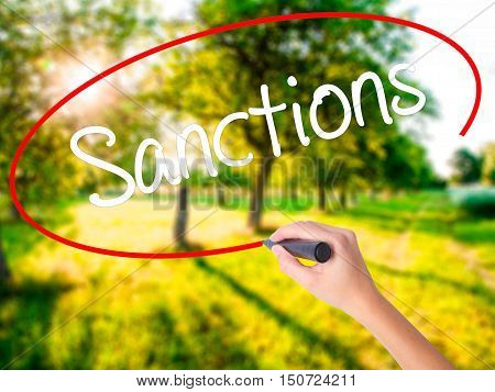 Woman Hand Writing Sanctions With A Marker Over Transparent Board .
