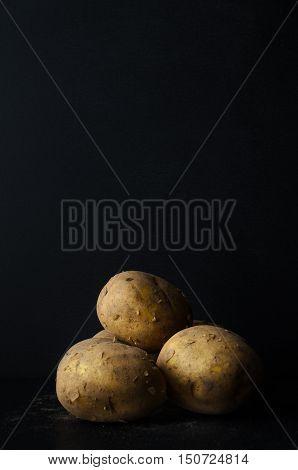 Potatoes Still Life On Black Slate With Soil Dusting