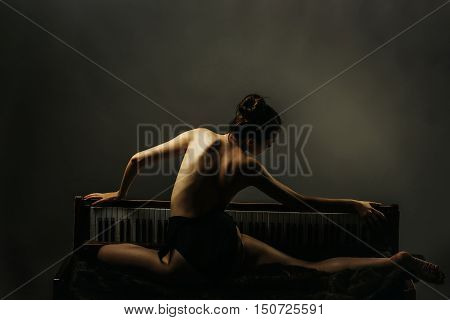 young woman dancer with sexy flexible body of ballerina and naked back posing on old retro wooden piano on grey background