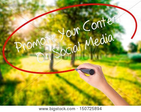 Woman Hand Writing Promote Your Content On Social Media  With A Marker Over Transparent Board