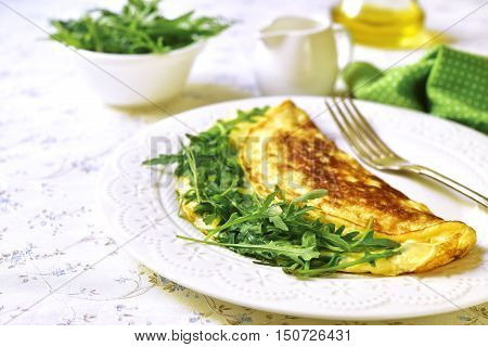 Omelet With Cheese And Arugula On A White Plate.
