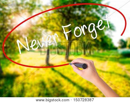 Woman Hand Writing Never Forget  With A Marker Over Transparent Board
