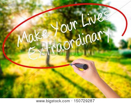 Woman Hand Writing Make Your Lives Extraordinary With A Marker Over Transparent Board