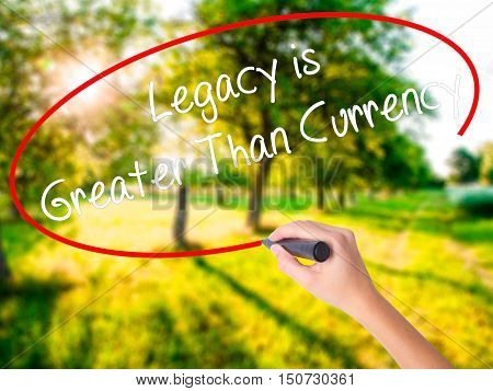 Woman Hand Writing Legacy Is Greater Than Currency With A Marker Over Transparent Board