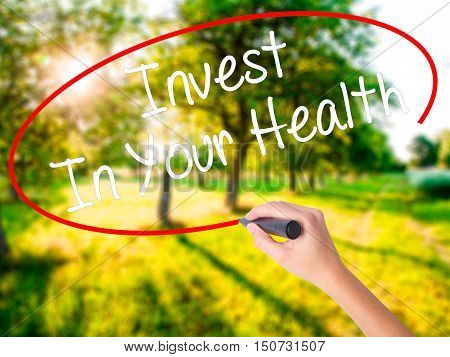Woman Hand Writing Invest In Your Health With A Marker Over Transparent Board .