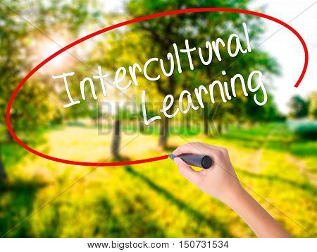 Woman Hand Writing Intercultural Learning With A Marker Over Transparent Board