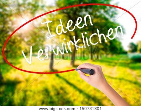 Woman Hand Writing Ideen Verwirklichen ( Realize Ideas In German) With A Marker Over Transparent Boa