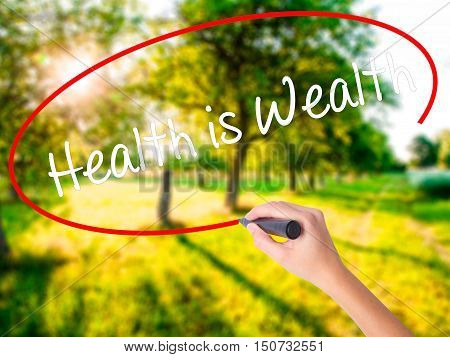 Woman Hand Writing Health Is Wealth With A Marker Over Transparent Board