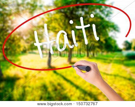 Woman Hand Writing Haiti With A Marker Over Transparent Board