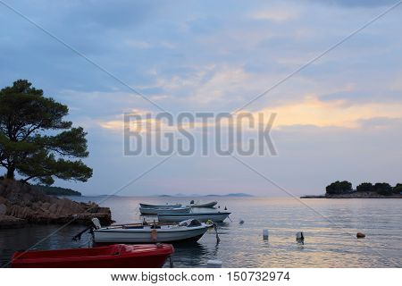 Colorful motor boats at anchor in calm blue sea water inshore after sunset on beautiful evening seascape