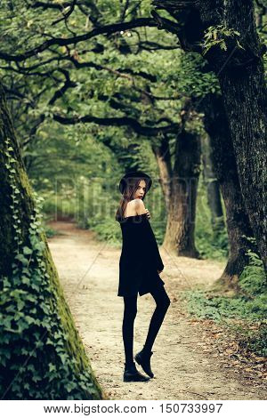 fashionable halloween young sexy woman or girl with red lips on pretty face in black witch hat tights and dress posing in deep green forest or wood outdoor on natural background
