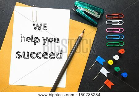 Text we help you succeed on white paper background / business concept