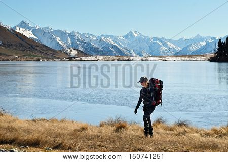 A Woman Hiker Walks Along Lake Clearwater. Hakatere Conservation Park, Souther Alps, New Zealand