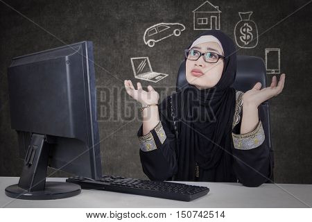 Arab business woman wearing glasses sitting in front of computer while doubting with her dream for buying something.