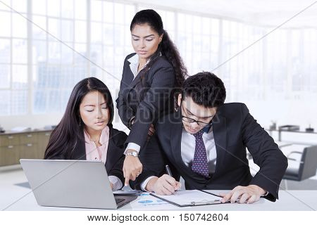 Portrait of the female team leader pointing to calculator with male employee is writing in the paperwork and female employee looking at the calculator and laptop on the table