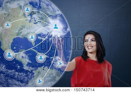 Young Asian woman is smiling and pressing icon of social media with network connection on the globe of virtual screen