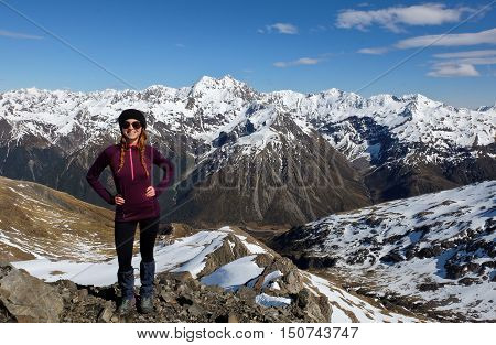 A Proud Woman Hiker Stands on a Mountain Summit.  Temple Basin, Arthurs Pass, Southern Alps, New Zealand