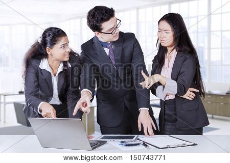 Portrait of troubled business people discussing report at meeting while pointing at the laptop with tablet and paperwork on the table