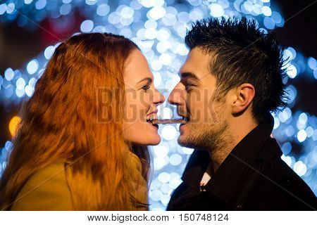 Couple eating together one piece of chocolate in street at night with christmas tree in background