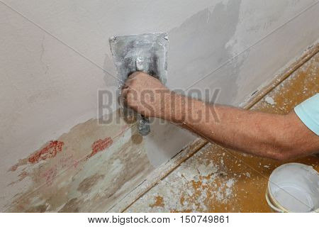 Worker Spreading Plaster To Damaged Wall
