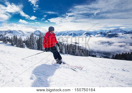 Young happy man skiing in Kitzbuehel ski resort and enjouing the beautiful weather with blue sky and Alpine mountains in Austria.