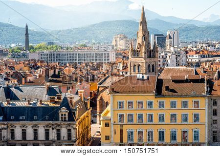 Cityscape view on the buildings with church tower and mountains in Grenoble city on the south-east of France