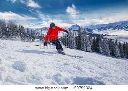 Young happy man skiing in Kitzbuehel ski resort and enjoying the beautiful weather with blue sky and Alpine mountains in Austria.