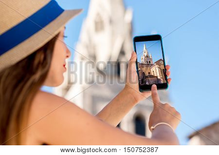 Young woman photographing with phone church's tower in Grenoble city in France. This tower is the main symbol of the city