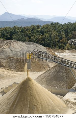 Working belt conveyors and a piles of rubble and stone meal in Gravel Quarry