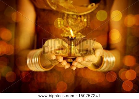 Close up Indian woman in traditional dress hands holding diya oil lamp and celebrating Diwali or deepavali, fesitval of lights.