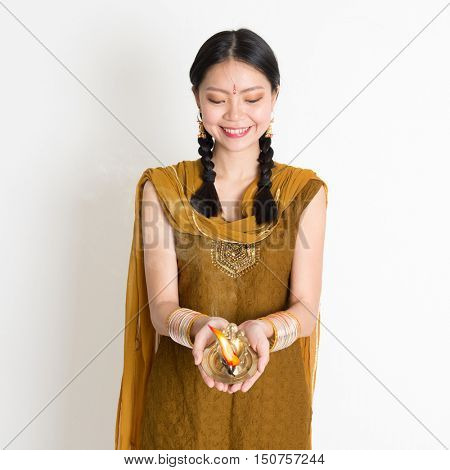 Young mixed race Indian Chinese woman in traditional dress hands holding diya oil lamp and celebrating Diwali or deepavali, fesitval of lights.