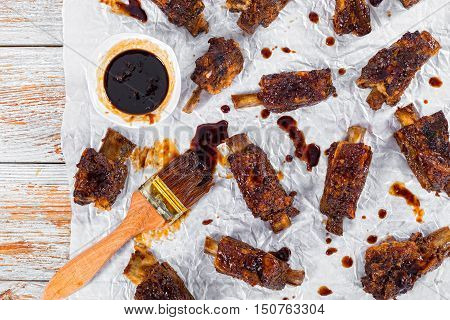 delicious hot sticky ribs seasoned with spicy soy garlic ginger barbecue sauce on parchment paper with brush on wooden peeling paint background view from above close-up