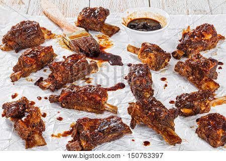 delicious hot sticky ribs seasoned with spicy soy garlic ginger barbecue sauce on parchment paper with brush on wooden peeling paint background top view close-up