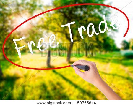 Woman Hand Writing Free Trade With A Marker Over Transparent Board