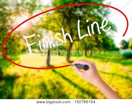 Woman Hand Writing Finish Line With A Marker Over Transparent Board
