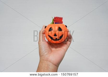 woman hold a bucket Jack-O-Lantern pumpkin full of candies