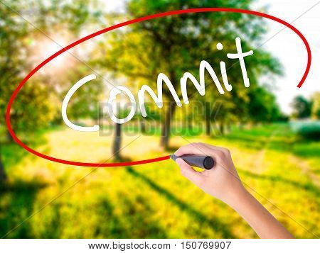 Woman Hand Writing Commit With A Marker Over Transparent Board