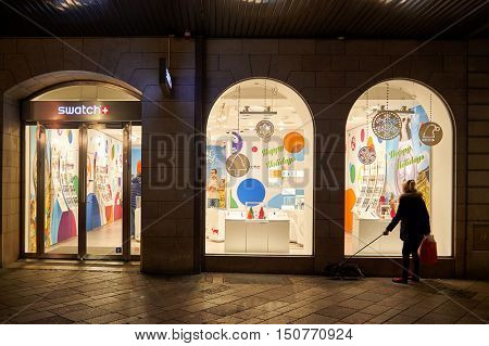GENEVA, SWITZERLAND - NOVEMBER 18, 2015: woman looking in a shop window at night. A shop window is a window in a shop displaying items for sale or otherwise designed to attract customers to the store.