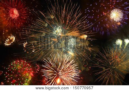Realistic Fireworks exploding with clouds of smoke in the night sky - bright festive background.