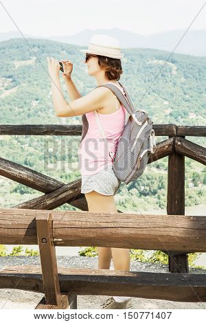Young traveller woman photographing with smartphone in ruin castle of Visegrad Hungary. Travel destination. Female portrait. Travelling theme.