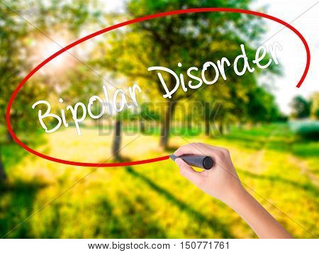Woman Hand Writing Bipolar Disorder With A Marker Over Transparent Board