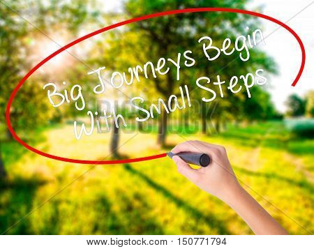 Woman Hand Writing Big Journeys Begin With Small Steps  With A Marker Over Transparent Board