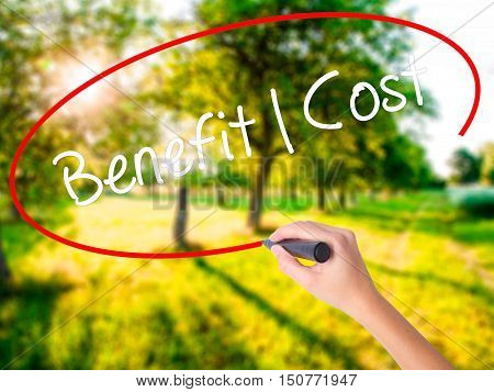 Woman Hand Writing Benefit Cost With A Marker Over Transparent Board